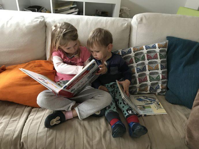 Geschwister beschäftigen sich gemeinsam Buchlesen